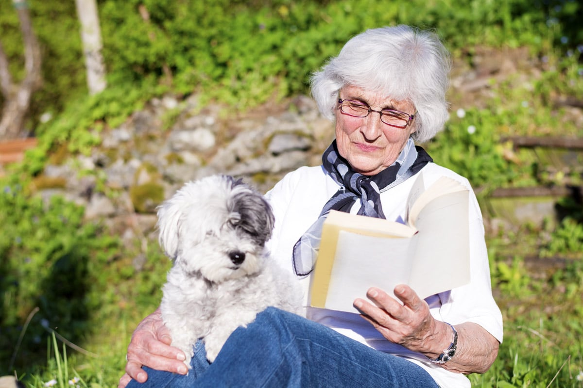 A Woman and her dog reading a book